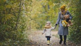 La petite fille joyeuse avec sa maman et nounours l'ours marche en parc d'automne Photo libre de droits