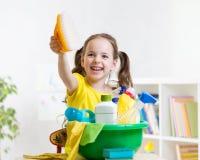 La petite fille joyeuse nettoie un plancher Images stock
