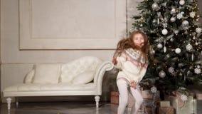 La petite fille joyeuse saute dans un hall près de l'arbre de Noël dans un matin de vacances clips vidéos