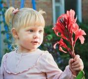 La petite fille la blonde retient une fleur Image stock