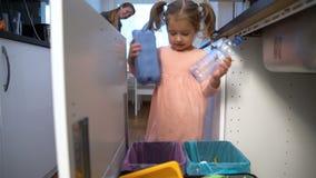 La petite fille laisse tomber les déchets dans le bac de recyclage de cuisine Mouvement lent chariot banque de vidéos