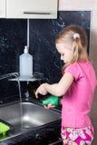 La petite fille lave des plats avec l'éponge Images libres de droits
