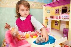 La petite fille lave une poupée dans le regroupement de la maison de jouet Image stock