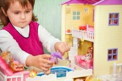 La petite fille lave une poupée dans le regroupement de la maison de jouet Photo stock