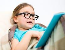 La petite fille lit un livre photos libres de droits