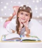 La petite fille lit un livre Photographie stock libre de droits
