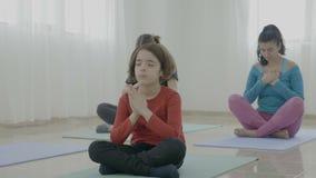 La petite fille méditant parmi le milieu a vieilli des femmes pendant une classe de yoga dans un studio de forme physique - clips vidéos