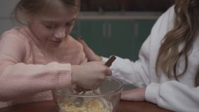 La petite fille mélange des oeufs à de la farine dans la cuvette se reposant à la table dans la cuisine avec sa soeur plus âgée D banque de vidéos
