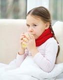 La petite fille malade boit le cocktail de vitamine photographie stock