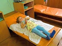La petite fille malade sur le traitement dans un bureau physiothérapique photographie stock