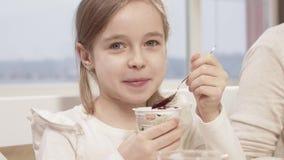 La petite fille mange d'une mousse de chocolat délicieuse pendant un dîner de famille banque de vidéos