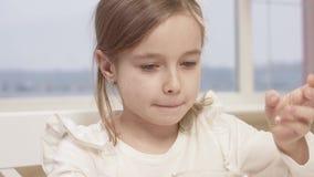 La petite fille mange d'une mousse de chocolat délicieuse pendant un dîner de famille clips vidéos