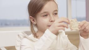 La petite fille mange du pain de riz pendant un dîner de famille banque de vidéos