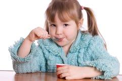La petite fille mange du yaourt Photos stock
