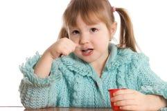 La petite fille mange du yaourt Photo stock