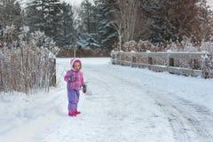 La petite fille marche dans la forêt de neige d'hiver sur la route Images stock