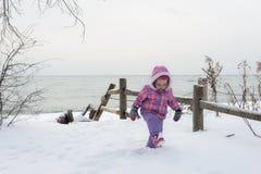 La petite fille marche dans la neige près du lac Ontario Photo stock