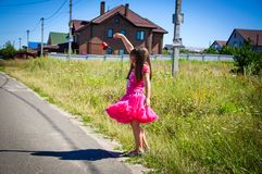 La petite fille marche sur la route dans le village Photo stock