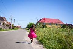 La petite fille marche sur la route dans le village Photographie stock libre de droits
