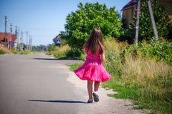 La petite fille marche sur la route dans le village Image stock