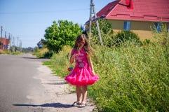 La petite fille marche sur la route dans le village Photographie stock