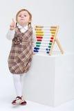 La petite fille menace le doigt à côté de l'abaque coloré Photo libre de droits