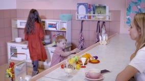 La petite fille mignonne apporte les fruits artificiels de jouet pour sa mère, se reposant au compteur dans l'appartement léger,  clips vidéos