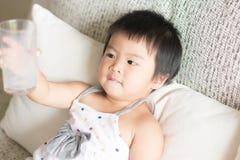 La petite fille mignonne asiatique est tenante et montrante un verre vide de images stock