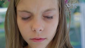 La petite fille mignonne avec la couronne du ` s de wildflower regarde et clignote l'appareil-photo 4K clips vidéos