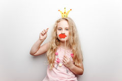 La petite fille mignonne avec la couronne de papier et les lèvres rouges s'assied sur la chaise rouge à la maison Photo libre de droits