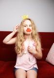 La petite fille mignonne avec la couronne de papier et les lèvres rouges s'assied sur la chaise rouge à la maison Photographie stock libre de droits