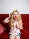La petite fille mignonne avec la couronne de papier et les lèvres rouges s'assied sur la chaise rouge à la maison Photo stock