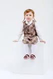 La petite fille mignonne avec les cheveux rouges s'assied sur le grand cube blanc Images libres de droits