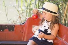 La petite petite fille mignonne avec un chapeau s'assied dans un bateau sur le lac Images libres de droits