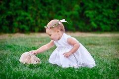 La petite fille mignonne avec un lapin a Pâques à l'herbe verte Photo stock