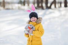 La petite fille mignonne avec un lapin a Pâques au fond blanc de neige Images stock