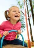 La petite fille mignonne balance sur la balançoir Photos libres de droits