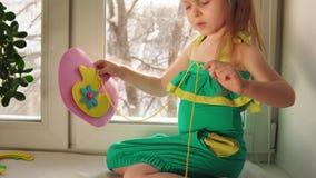 La petite fille mignonne coud un sac à main rose banque de vidéos