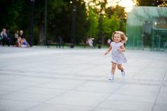 La petite fille mignonne court autour de la place en parc de ville images libres de droits