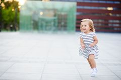 La petite fille mignonne court autour de la place en parc de ville images stock
