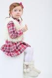 La petite fille mignonne dans des bottes de fourrure s'assied sur le cube Photo libre de droits