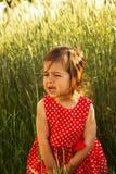 La petite fille mignonne dans la robe rouge pleure dans le jour d'été Images stock