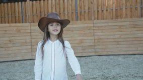 La petite fille mignonne dans le chapeau marche et pose avec le sourire sur l'hippodrome clips vidéos