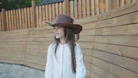 La petite fille mignonne dans le chapeau marche et regarde autour avec le sourire sur l'hippodrome banque de vidéos