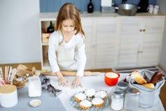 La petite fille mignonne dans le tablier fait cuire des biscuits dans la cuisine image stock
