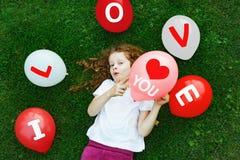 La petite fille mignonne dans un T-shirt blanc, tiennent un ballon rouge Images libres de droits