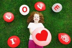 La petite fille mignonne dans un T-shirt blanc, tiennent un ballon rouge avec Photographie stock libre de droits