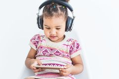 La petite fille mignonne dans une robe multicolore, écoute la musique avec des écouteurs et utilise un smartphone sur un fond bla images stock