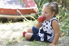 La petite fille mignonne dans une robe s'assied par le lac et mange une pomme Photos libres de droits