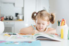 La petite fille mignonne dessine avec le crayon coloré à la maison images stock